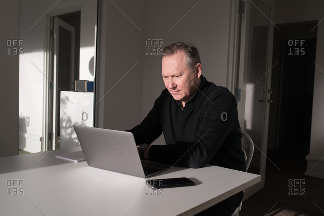 Older businessman working on a laptop