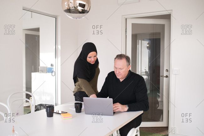 Older businessman working at computer with female coworker wearing a hijab