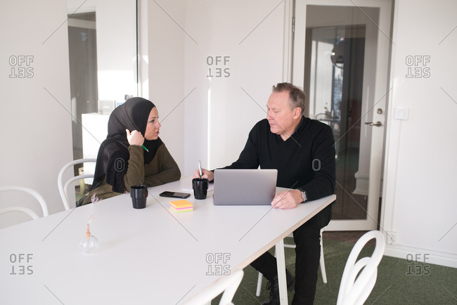 Older businessman in discussion with female coworker wearing hijab