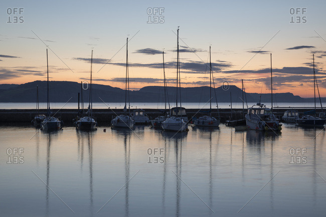 Lyme Regis, Dorset, England, United Kingdom, Europe - September 18, 2017: Yachts moored in The Cobb with Jurassic Coast and Golden Cap at sunrise