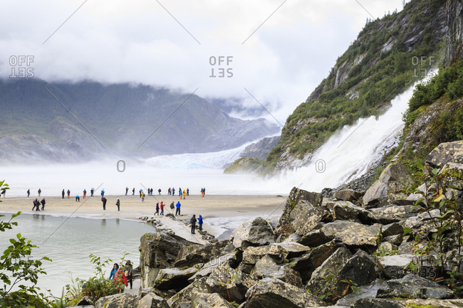Juneau, Alaska, United States of America, North America - August 30, 2017: Mendenhall Glacier and Lake, Nugget Falls Cascade, mist, visitors on a beach, Nugget Falls Trail