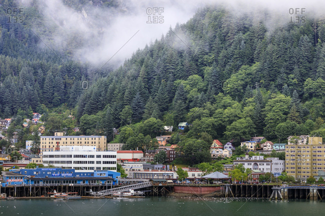 Juneau, Alaska, United States of America, North America - August 30, 2017: Juneau, State Capital, view from the sea, mist clears over downtown buildings, mountains, forest and float planes