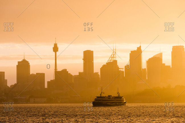 Sydney, New South Wales, Australia, Pacific - March 9, 2017: Sydney city skyline looking towards the sun with ferry
