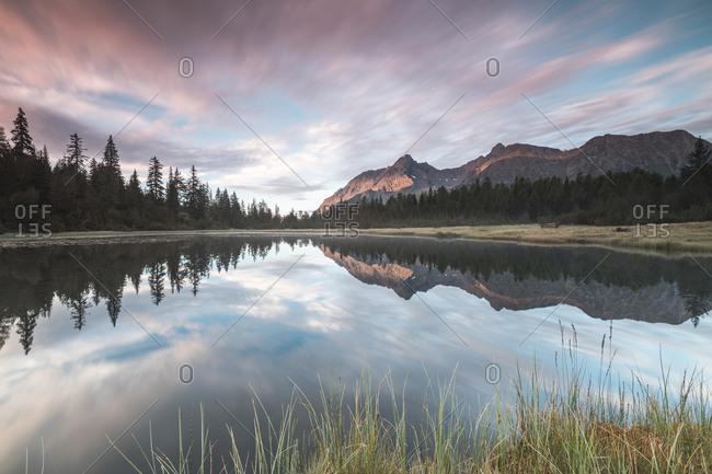 Clouds reflected in Lake Entova at dawn, Entova Alp, Malenco Valley, Sondrio province, Valtellina, Lombardy, Italy, Europe