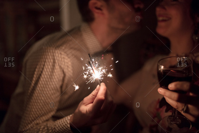 Man leaning in to kiss a laughing woman as sparklers burn
