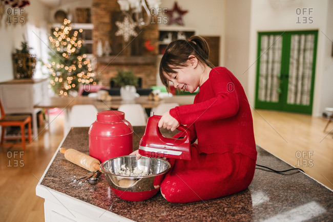 Young girl helping mix dough for Christmas cookies