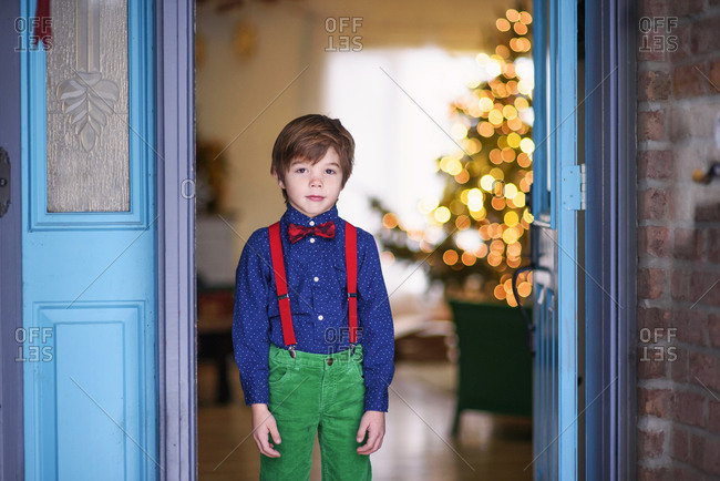 Little boy at front door dressed in a suspender and bowtie