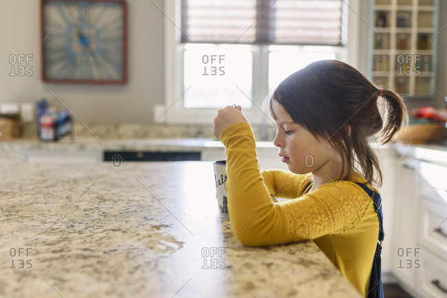 Young girl drinking hot drink in a kitchen
