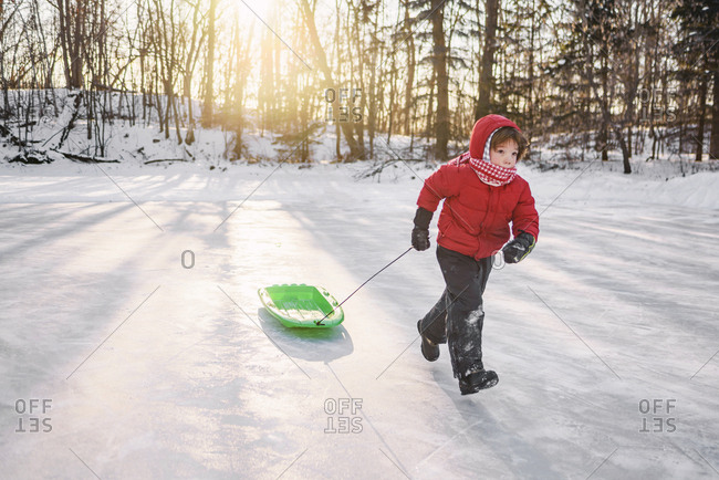 Young boy running with sled in the snow