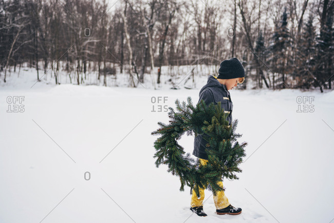 Young boy outside holding holiday wreath