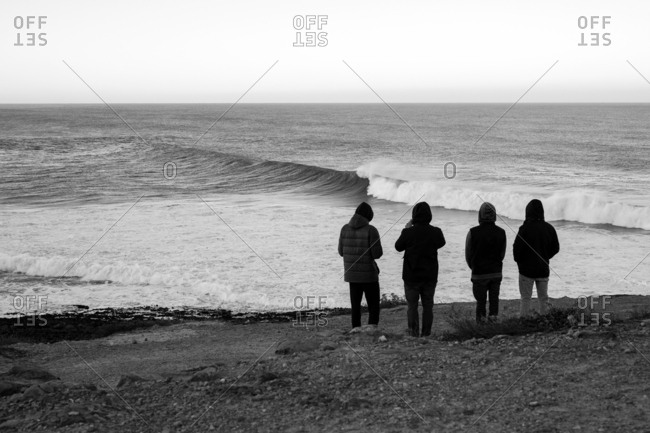 Four people looking out at cresting ocean waves