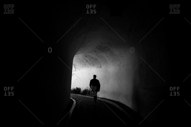 Man walking in tunnel in black and white