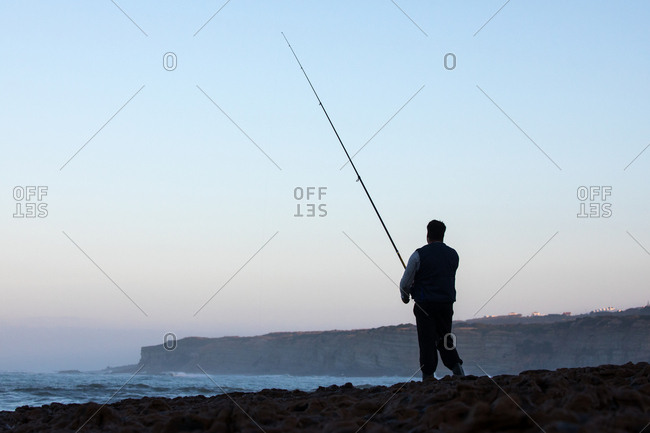 Man fishing on rocky beach