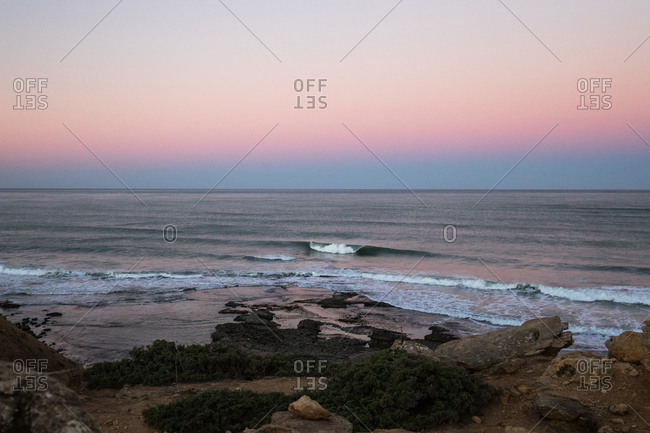 Rolling waves under sunset sky