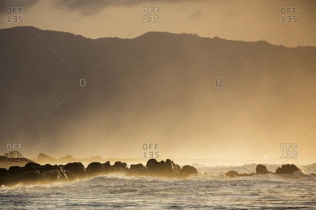 Splashing waters on rocky shore at sunrise