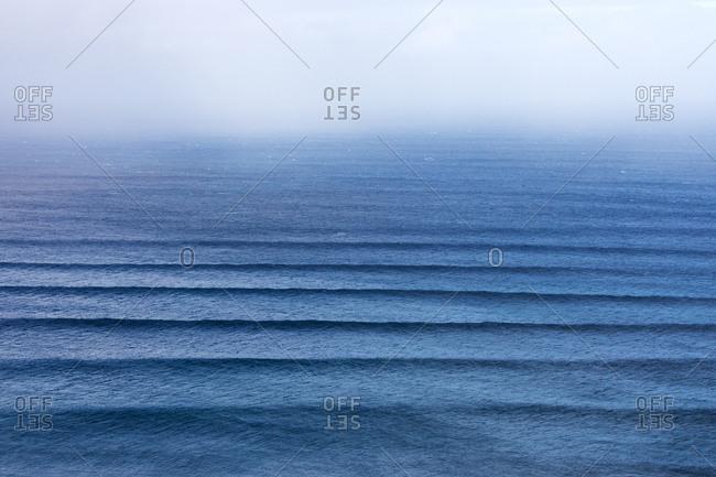 Ripples in the ocean under foggy sky