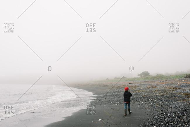 Boy walking alone along the beach on a foggy day