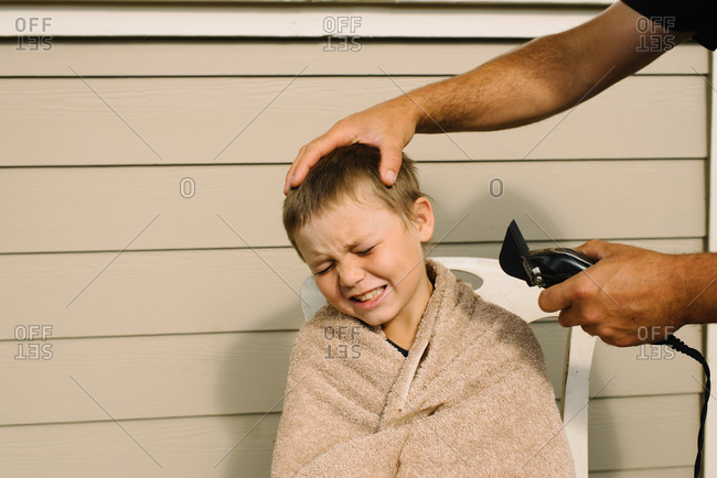 Person about to use clippers to give boy a haircut