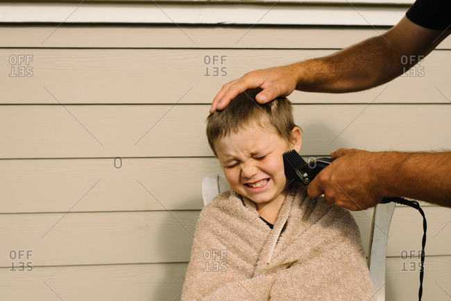 Boy getting a buzz cut with hair clippers