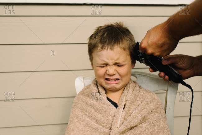 Boy getting a buzz cut with clippers