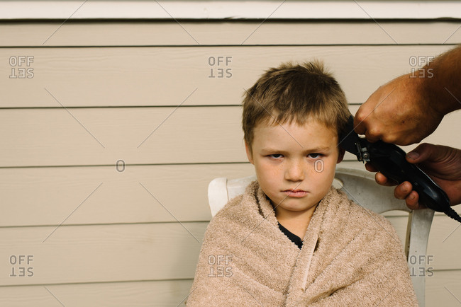 Person giving boy a haircut