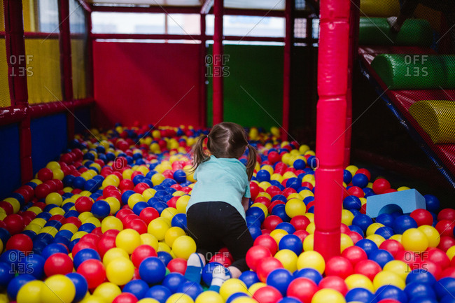 Little girl playing in a ball pit