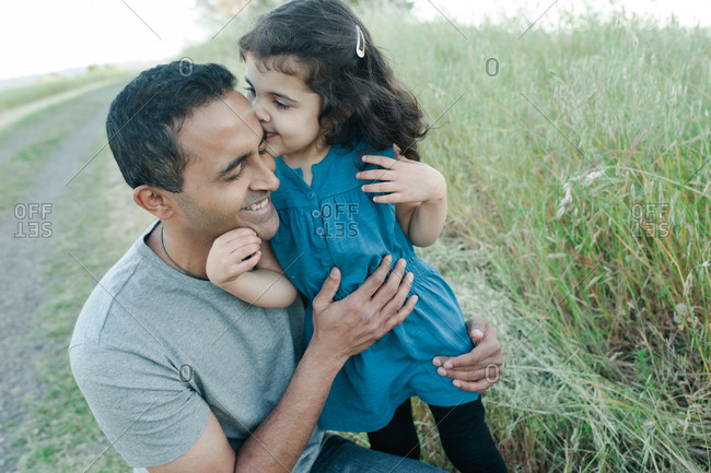 Girl giving her father a kiss in a field of grass