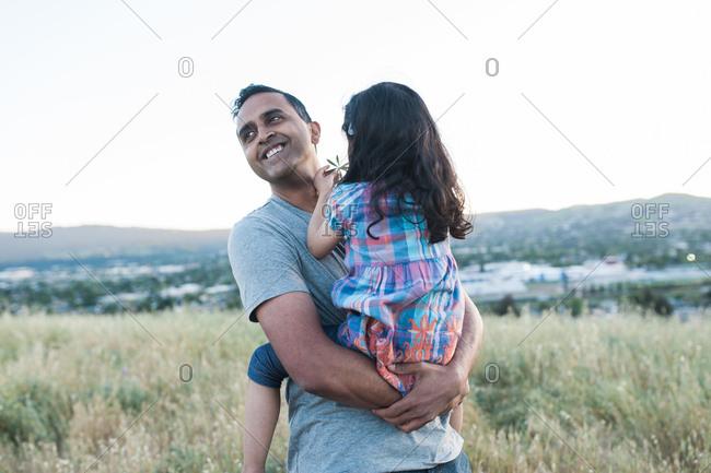 Smiling man carrying his daughter