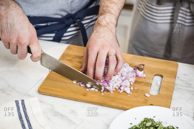 Man chopping onions during a cookery class