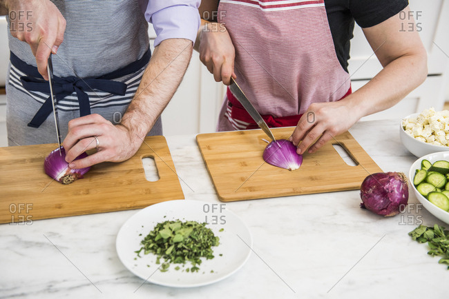 Chopping onions side by side during a cookery class