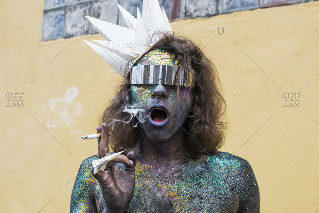 Brooklyn, NY, USA - June 16, 2017: Portrait of man smoking and painted as aquatic character at the Mermaid Parade in Coney Island