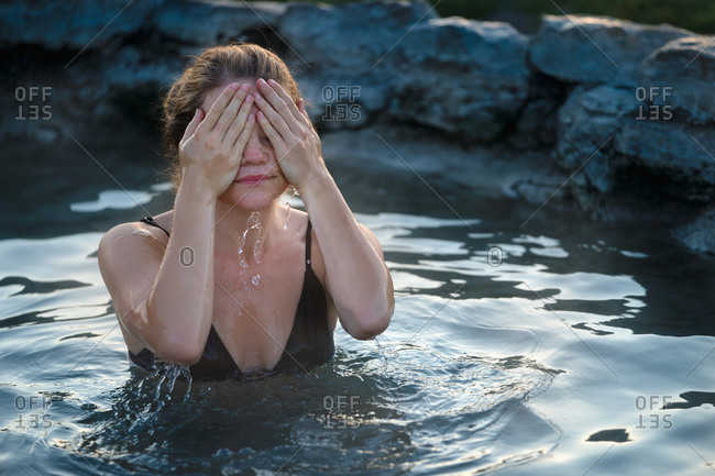 Woman Covering Face While Relaxing In Hot Spring