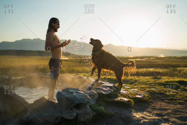 Shirtless Young Man Playing With Dog In Hot Spring