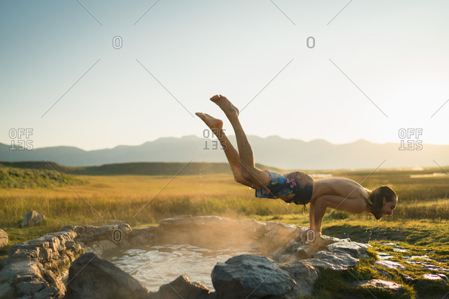 Young Man Performing Handstand Over Hot Spring