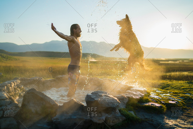 Dog Jumping Towards Man Standing In Hot Spring