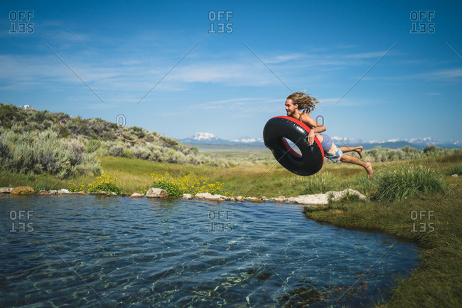 Man With Inflatable Ring Jumping In Lake
