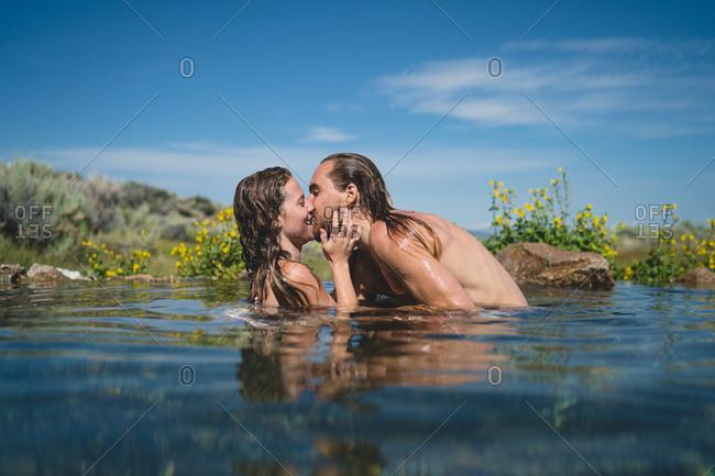 Man Kissing Woman While Enjoying In Lake