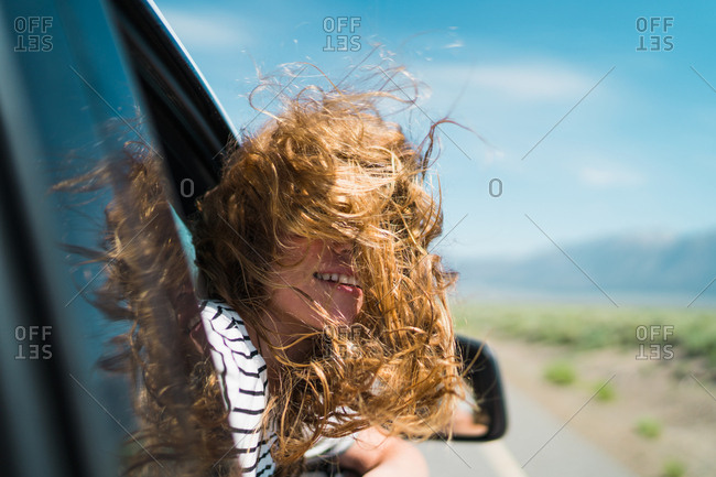 Woman With Windswept Hair Enjoying Road Trip In Car