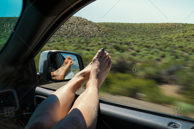 Woman With Legs On Window Enjoying Road Trip In Car