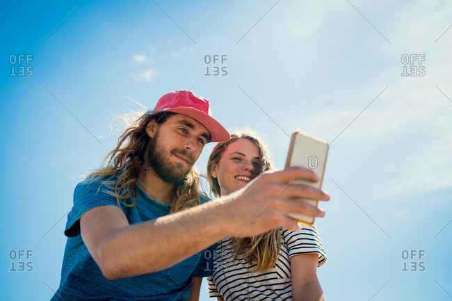 Couple Taking Selfie On Smartphone Against Sky During Summer
