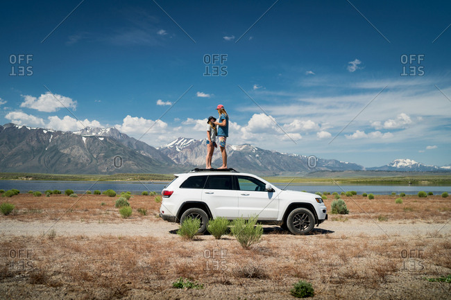 Couple Standing On Car Against Mountains