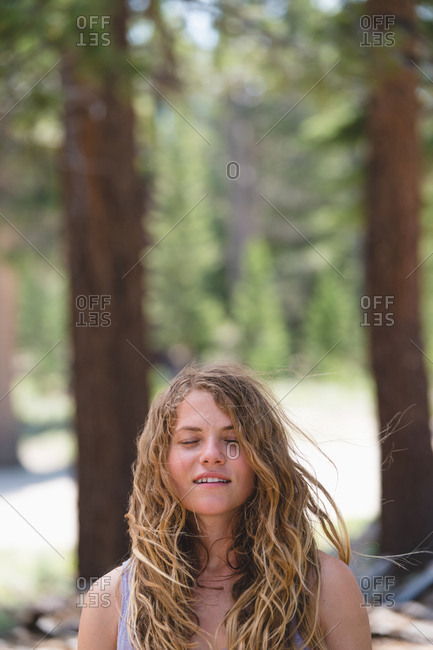 Woman Enjoying Wind While Standing In Forest