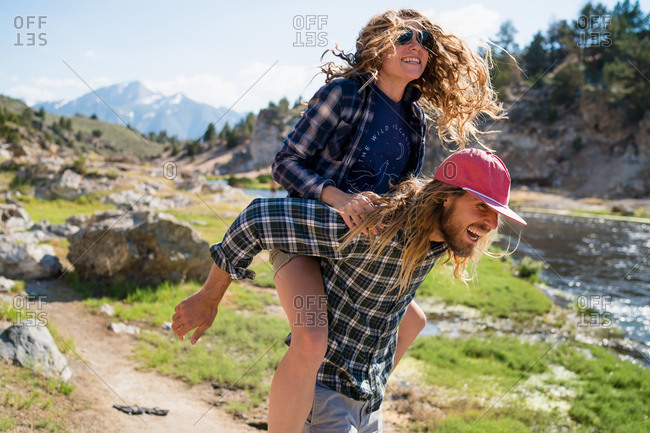 Hiker Giving Piggyback Ride To Woman In Forest