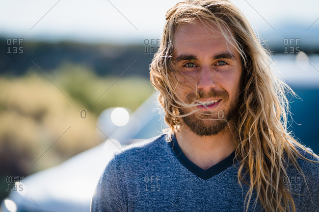 Man With Long Blond Hair Smiling On Sunny Day