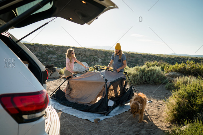 Couple Setting Up Tent On Field