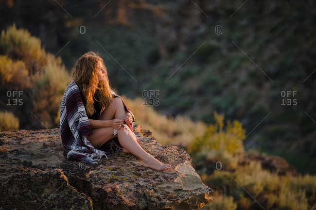 Woman Sitting On Cliff While Looking At View