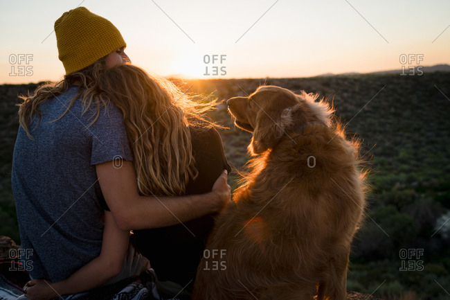 Dog Looking At Couple Embracing On Mountain During Sunset