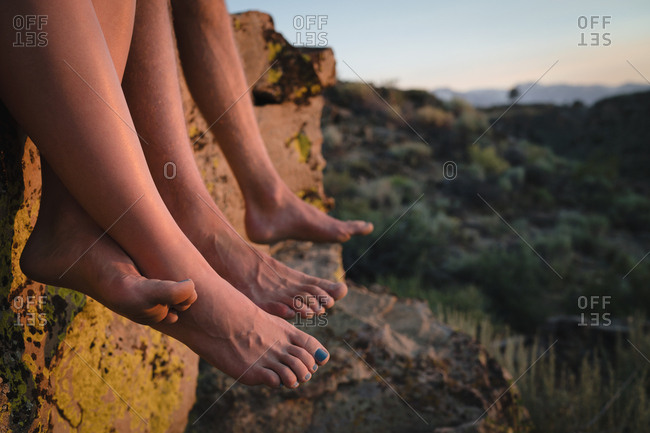 Cropped shot of hikers bare feet dangling over rocks