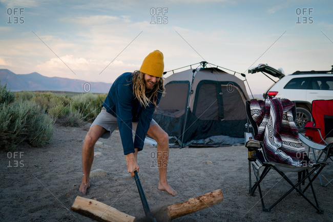 Hiker Cutting Wood With Axe At Campsite