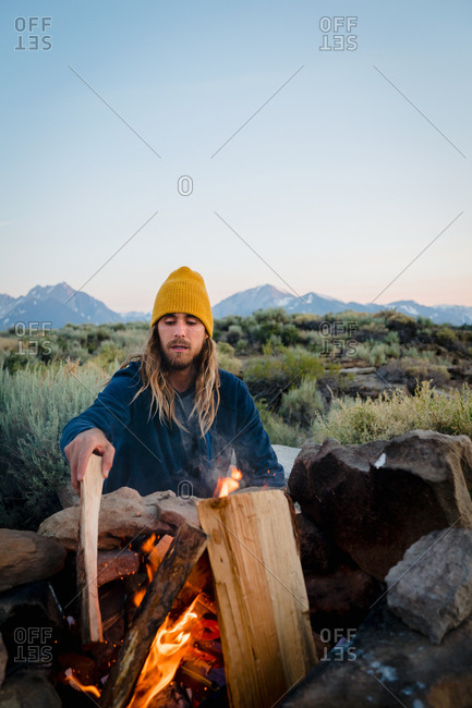 Man starting a fire at campsite